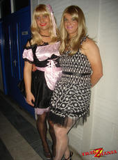 Two sexy blonde crossdressers posing at a fetish club
